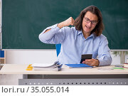Young male teacher in front of green board. Стоковое фото, фотограф Elnur / Фотобанк Лори
