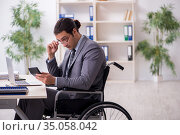 Young male employee in wheel-chair. Стоковое фото, фотограф Elnur / Фотобанк Лори