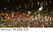 Multicoloured glitter gems falling on black background. Стоковое видео, агентство Wavebreak Media / Фотобанк Лори