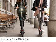 Unrecognizable trendy fashinable teenager girls riding public rental electric scooters in urban city environment. New eco-friendly modern public city transport in Ljubljana, Slovenia. Стоковое фото, фотограф Matej Kastelic / Фотобанк Лори
