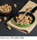 Leguminous plant is a source of vitamins, antioxidants, iron, hemoglobin and fiber, walnut contains niacin B3, roasted peanuts in shells in a frying pan on a table on a black concrete background. Стоковое фото, фотограф Светлана Евграфова / Фотобанк Лори