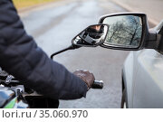 Motorcyclist does not keep distance while riding side by side with a car, side mirrors touching. Стоковое фото, фотограф Кекяляйнен Андрей / Фотобанк Лори