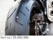 Puncture of rear wheel of motorcycle, steel screw is in tyre, horizontal image. Стоковое фото, фотограф Кекяляйнен Андрей / Фотобанк Лори