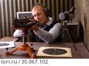 Shooter practicing shotgun shooting in sitting position at firing range. Стоковое фото, фотограф Яков Филимонов / Фотобанк Лори