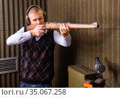 Confident shooter sighting in or zeroing shotgun in shooting gallery. Стоковое фото, фотограф Яков Филимонов / Фотобанк Лори