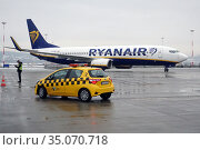 Krakow, Poland, Boeing 737 of Ryanair, Follow me-Car and Ramp Agent on the apron of John Paul II Krakow-Balice Airport (2019 год). Редакционное фото, агентство Caro Photoagency / Фотобанк Лори