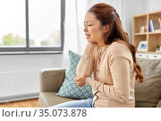 asian woman suffering from ache in hand at home. Стоковое фото, фотограф Syda Productions / Фотобанк Лори
