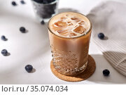 glass of ice coffee on cork drink coaster. Стоковое фото, фотограф Syda Productions / Фотобанк Лори