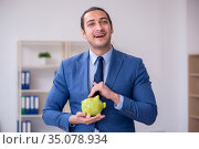 Young male employee in budget planning concept. Стоковое фото, фотограф Elnur / Фотобанк Лори
