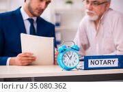 Young male lawyer and old man in testament and time management c. Стоковое фото, фотограф Elnur / Фотобанк Лори