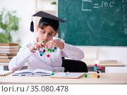 Young graduate holding molecular model in the classroom. Стоковое фото, фотограф Elnur / Фотобанк Лори