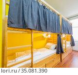 Hostel dormitory beds arranged in room. Стоковое фото, фотограф Elnur / Фотобанк Лори