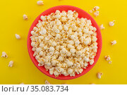 High angle view of popcorn in red bowl on yellow background. Стоковое фото, агентство Wavebreak Media / Фотобанк Лори