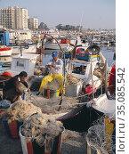Fiskare i Larnakas hamn, kontrollerar sina nät. Cypern.Photo: André... Редакционное фото, фотограф Andre Maslennikov / age Fotostock / Фотобанк Лори