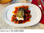 cuisine spanish candied fish with stewed vegetables served on white plate. Стоковое фото, фотограф Яков Филимонов / Фотобанк Лори