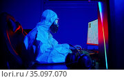 A man in white protective costume and a respirator playing game in gaming club. Стоковое видео, видеограф Константин Шишкин / Фотобанк Лори