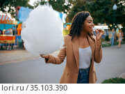 Cheerful woman with cotton candy in amusement park. Стоковое фото, фотограф Tryapitsyn Sergiy / Фотобанк Лори