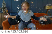 Happy woman celebrates with golden and silver confetti at home sitting on the orange sofa on dark blue wall background, smilling girl throwing small pieces of confetti. Стоковое видео, видеограф Ольга Балынская / Фотобанк Лори