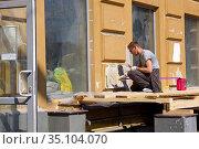 Ремонт здания. Рабочий штукатурит внешнюю стену (2019 год). Редакционное фото, фотограф ирина реброва / Фотобанк Лори