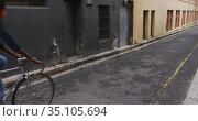 African american woman wearing face mask riding bicycle in street. Стоковое видео, агентство Wavebreak Media / Фотобанк Лори