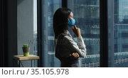 Thoughtful asian woman wearing face mask looking out of window at modern office. Стоковое видео, агентство Wavebreak Media / Фотобанк Лори