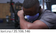 Fit african american man wearing face mask sneezing on his elbow in the gym. Стоковое видео, агентство Wavebreak Media / Фотобанк Лори