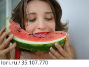 Close up indoors portrait of beautiful woman with short hair and sensual lips eating a piece of watermelon. Hedonism, happiness and buoyancy. Стоковое фото, фотограф Ольга Балынская / Фотобанк Лори