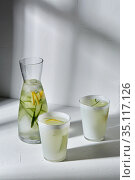 glasses with lemon water and cucumber on table. Стоковое фото, фотограф Syda Productions / Фотобанк Лори