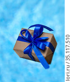 Flying in the air gift box tied with a ribbon on a blue background with space for text. Festive layout. Стоковое фото, фотограф Иван Карпов / Фотобанк Лори