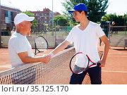 mature senior and young man shake hands before tennis match. Стоковое фото, фотограф Татьяна Яцевич / Фотобанк Лори