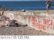 """Бетонный пирс на пляже Толстяк с надписью """"Не курить! Прыгать с пирса запрещено!"""" в городе Севастополе, Крым. Редакционное фото, фотограф Николай Мухорин / Фотобанк Лори"""