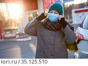 Caucasian woman a driver puts on a facial mask before refuel a car and make payment on petrol station. Стоковое фото, фотограф Кекяляйнен Андрей / Фотобанк Лори
