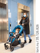 Adult mother wearing medical mask coming from elevator with children stroller, a hall of shopping mall. Стоковое фото, фотограф Кекяляйнен Андрей / Фотобанк Лори