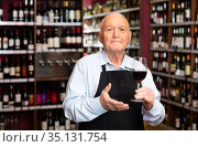 Confident elderly male winemaker inviting to wine house, offering glass of wine for tasting. Стоковое фото, фотограф Яков Филимонов / Фотобанк Лори