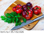 Beefsteak tomatoes and parsley on wooden table. Стоковое фото, фотограф Яков Филимонов / Фотобанк Лори