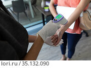 Mixed race woman wearing surgical gloves checking temperature of female colleague. Стоковое фото, агентство Wavebreak Media / Фотобанк Лори