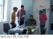 Diverse group of colleagues wearing face masks discussing in office. Стоковое фото, агентство Wavebreak Media / Фотобанк Лори