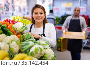 Salesgirl standing near fresh cauliflower and vegetables in store. Стоковое фото, фотограф Яков Филимонов / Фотобанк Лори