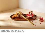 croissant, pomegranate and honey on wooden tray. Стоковое фото, фотограф Syda Productions / Фотобанк Лори