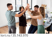 happy business team making high five at office. Стоковое фото, фотограф Syda Productions / Фотобанк Лори
