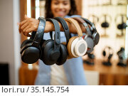 Woman shows headphones collection in audio store. Стоковое фото, фотограф Tryapitsyn Sergiy / Фотобанк Лори