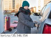 Caucasian woman opening cap lid of car tank on petrol station, winter season, female looking at camera. Стоковое фото, фотограф Кекяляйнен Андрей / Фотобанк Лори