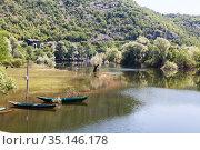 Fishing boats moored on overflowed bank of the Rijeka Crnojevica town. It is near the coast of Skadar lake. The Balkan Peninsula, Montenegro (2016 год). Стоковое фото, фотограф Кекяляйнен Андрей / Фотобанк Лори