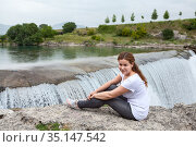 Portrait of attractive woman resting close to waterfall of the Cijevna river. It is called Montenegrin Niagara Falls. Surroundings of Podgorica city. Montenegro, Europe. Стоковое фото, фотограф Кекяляйнен Андрей / Фотобанк Лори