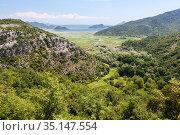 The Rijeka Crnojevica river mouth in lake Skadar. Wetlands around hills and mountains. Montenegro (2016 год). Стоковое фото, фотограф Кекяляйнен Андрей / Фотобанк Лори