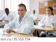 Cheerful man in white coat sitting at lecture during refresher course. Стоковое фото, фотограф Яков Филимонов / Фотобанк Лори