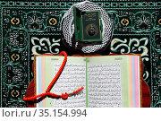 Open Quran on Muslim prayer mat at home. France. Стоковое фото, фотограф Fred de Noyelle / Godong / age Fotostock / Фотобанк Лори
