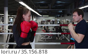 Gym training - young pretty woman training her boxing on the ring with trainer. Стоковое видео, видеограф Константин Шишкин / Фотобанк Лори