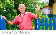 gray haired man in red pollo swearing near fence in countryside. Стоковое фото, фотограф Татьяна Яцевич / Фотобанк Лори