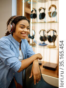 Young woman listening to music, headphones store. Стоковое фото, фотограф Tryapitsyn Sergiy / Фотобанк Лори